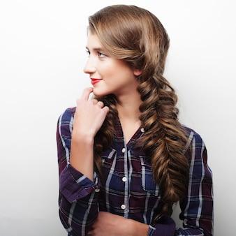 Ritratto di una giovane donna con una treccia su sfondo bianco
