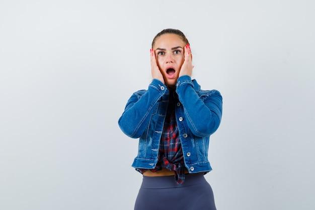 Ritratto di giovane donna con le mani sulle guance in camicia, giacca e vista frontale scioccata