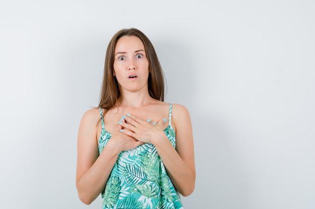 Ritratto di giovane donna con le mani sul petto in camicetta e guardando perplesso vista frontale