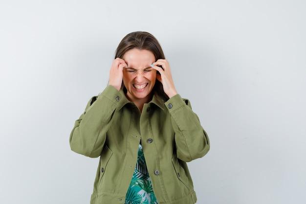 Ritratto di giovane donna con le mani sulla testa in giacca verde e dall'aspetto irritato vista frontale