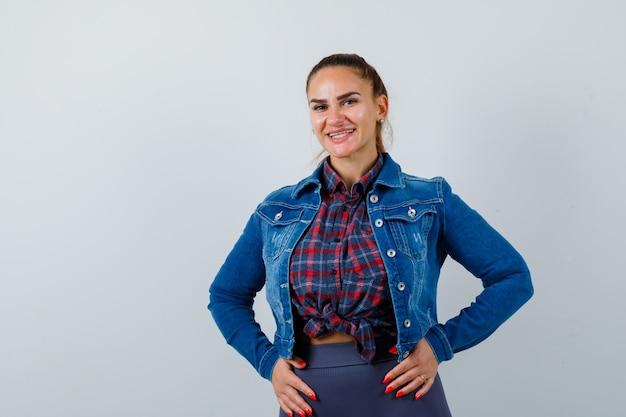 Ritratto di giovane donna con le mani sullo stomaco in camicia, giacca e guardando la vista frontale allegra