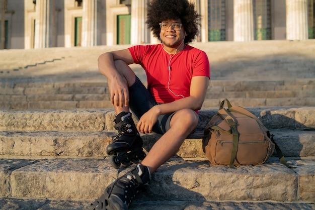 Ritratto di giovane uomo latino ascoltando musica con gli auricolari e riposando dopo il pattinaggio a rotelle all'aperto