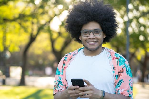 Ritratto di giovane uomo latino utilizzando il suo telefono cellulare in piedi all'aperto sulla strada. concetto urbano.