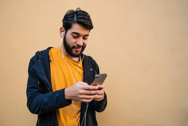 Ritratto di giovane uomo latino utilizzando il suo telefono cellulare con gli auricolari. concetto di comunicazione.