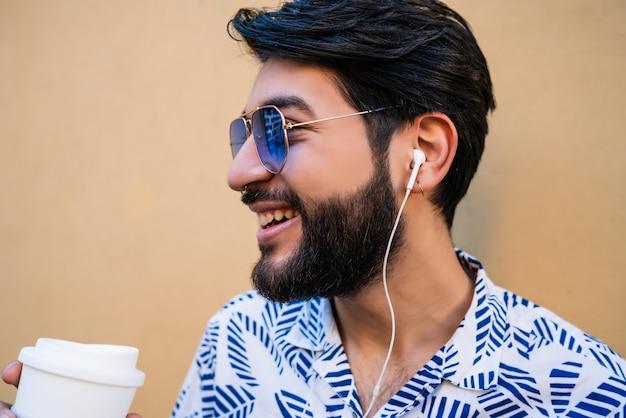 Ritratto di giovane uomo latino che indossa abiti estivi, che tiene una tazza di caffè e ascolta la musica con gli auricolari su sfondo giallo.