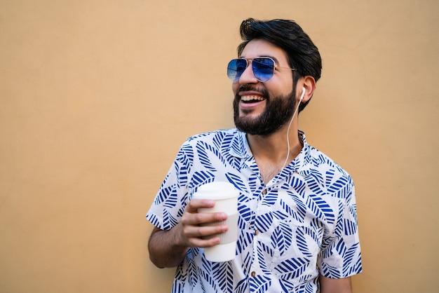 Ritratto di giovane uomo latino che indossa abiti estivi, che tiene una tazza di caffè e ascolta la musica con gli auricolari.