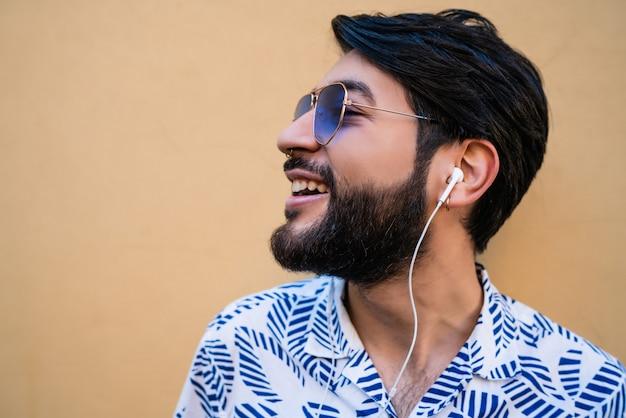 Ritratto di giovane uomo latino che indossa abiti estivi e ascolto di musica con gli auricolari.