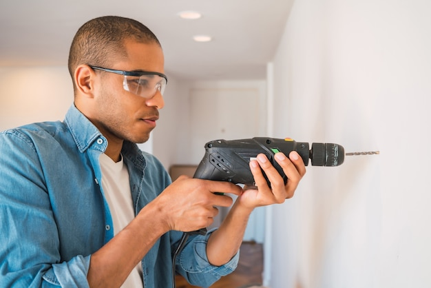 Ritratto di giovane uomo latino con un trapano elettrico e fare un buco nel muro. interior design e concetto di ristrutturazione della casa.