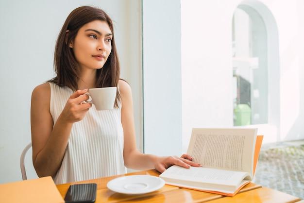 Ritratto di giovane donna latina godendo e bevendo una tazza di caffè al bar. concetto di stile di vita.