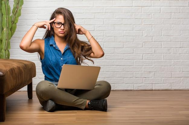 Ritratto di giovane donna latina che si siede sul pavimento uomo facendo un gesto di concentrazione