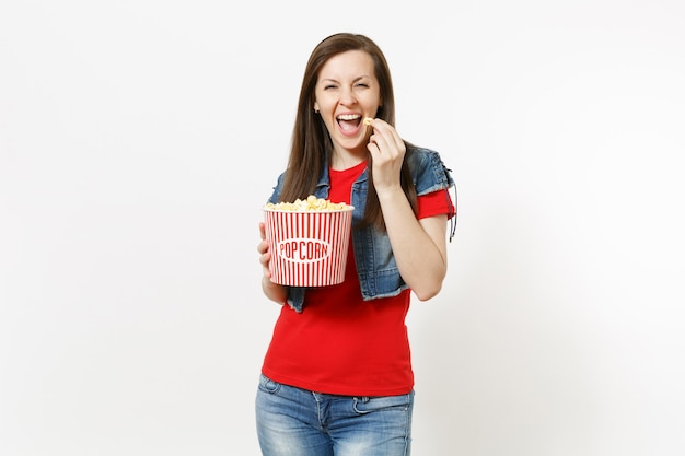 Ritratto di giovane bella donna castana divertente di risata in abbigliamento casual che guarda film di film, che tiene e che mangia popcorn dal secchio isolato su fondo bianco. emozioni nel concetto di cinema.