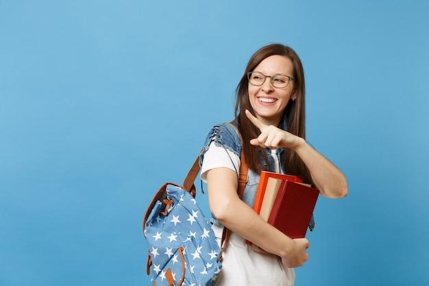 Ritratto di giovane studentessa che ride in bicchieri con zaino che tiene libri, puntando il dito indice lontano, guarda da parte isolato su sfondo blu. istruzione nel concetto di college universitario di liceo.