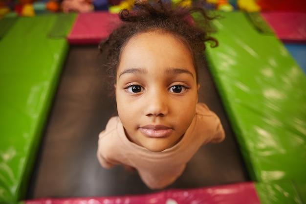 Ritratto di giovane bambina guardando davanti mentre salta sul trampolino nel parco di divertimenti
