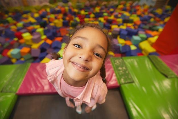 Ritratto di giovane bambina sorridente nella parte anteriore durante la riproduzione nel centro del trampolino