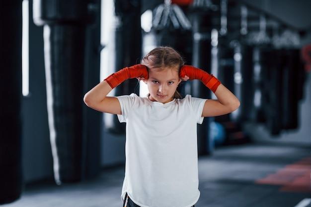 Ritratto di giovane bambina in abbigliamento sportivo che è in palestra ha una giornata di esercizio. concezione della boxe.