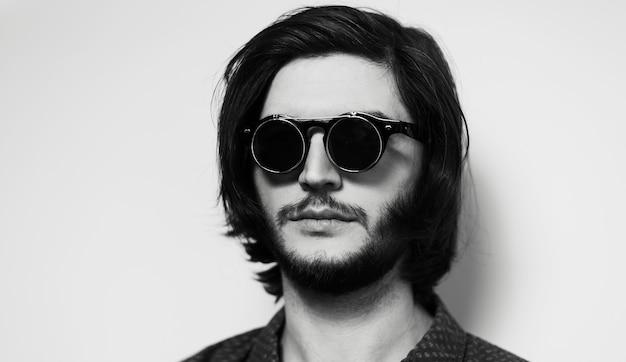 Ritratto di giovane uomo dai capelli lunghi con sfumature nere.