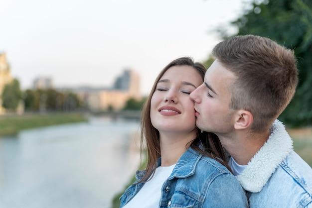 Ritratto di giovane coppia amorosa sul fiume. guy bacia la sua amata sulla guancia. appuntamento romantico.