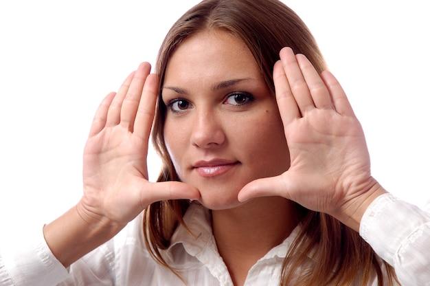 Ritratto di una giovane ragazza magnifica con trucco naturale, capelli lunghi castani, vestiti semplici bianchi, mostra le palme vicino al viso