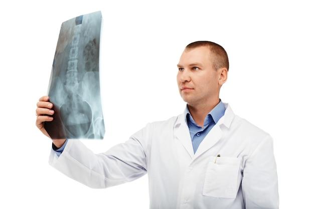 Ritratto di un giovane medico maschio in camice bianco contro un bianco