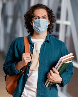 Ritratto di giovane studente maschio che indossa una mascherina medica