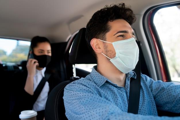 Ritratto di giovane tassista maschio con un passeggero di donna d'affari sul sedile posteriore