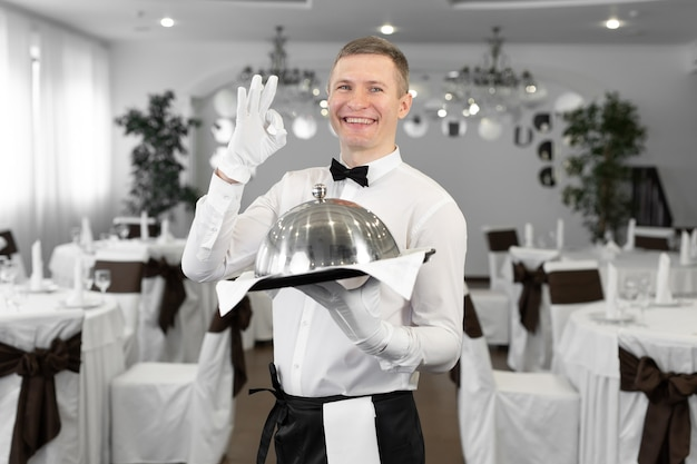 Ritratto di un giovane cameriere maschio in uniforme che mostra il segno
