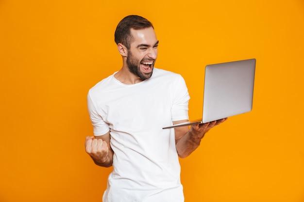 Ritratto di giovane uomo 30s in maglietta bianca che tiene computer portatile d'argento, isolato