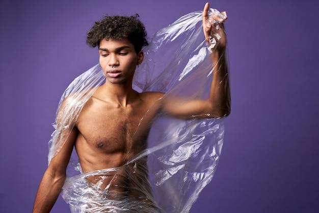 Ritratto di giovane uomo rompere il sacchetto di plastica con le mani atletiche transgender latino maschio occhi chiusi
