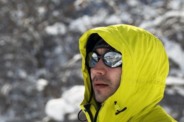 Ritratto di giovane uomo in giacca giallo brillante che indossa occhiali a specchio con la riflessione di montagna. copia spazio