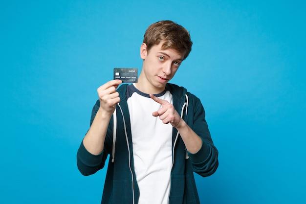 Ritratto di giovane uomo in abiti casual che tiene, puntando il dito indice sulla carta bancaria di credito isolata sulla parete blu. persone sincere emozioni, concetto di stile di vita.