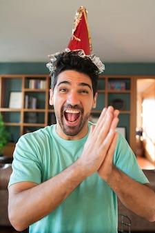 Ritratto di giovane uomo che celebra il suo compleanno in una videochiamata mentre si è a casa. nuovo concetto di stile di vita normale.