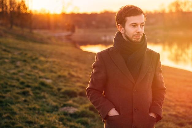 Ritratto di un giovane uomo in un cappotto che cammina nel bosco. giovane che cammina nella foresta giornata di sole primaverile.