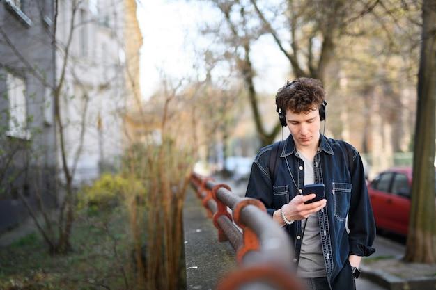 Ritratto di giovane pendolare con le cuffie che cammina all'aperto in città, utilizzando lo smartphone.