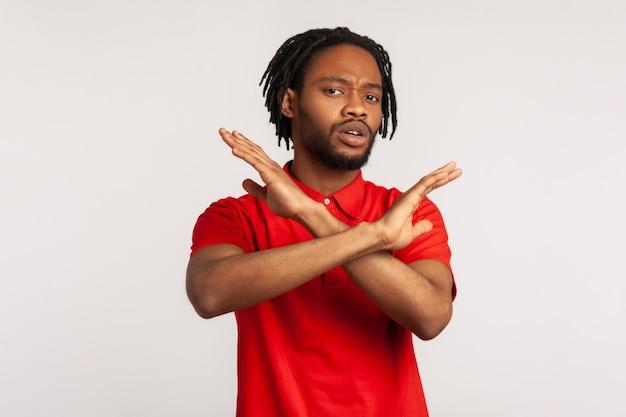 Ritratto di giovane uomo che incrocia le mani, gesticolando avvertimento o divieto, che significa fermata fine.