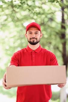 Ritratto di giovane uomo che consegna pacchi
