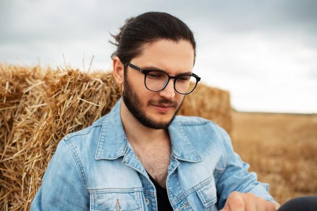 Ritratto di giovane uomo in giacca di jeans vicino a mucchi di fieno.