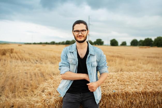 Ritratto di giovane uomo in giacca di jeans in piedi vicino a mucchi di fieno nel campo.