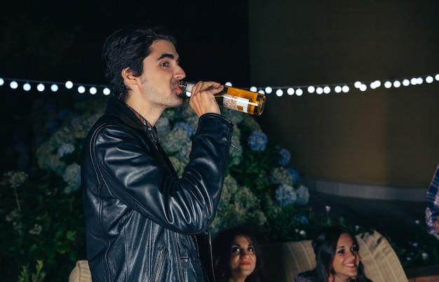 Ritratto di giovane uomo che beve una bottiglia di birra mentre si diverte con i suoi amici in una festa all'aperto. concetto di amicizia e celebrazioni.