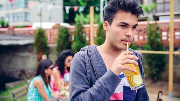 Ritratto di giovane uomo che beve cocktail di acqua infusa all'aperto con i suoi amici seduti