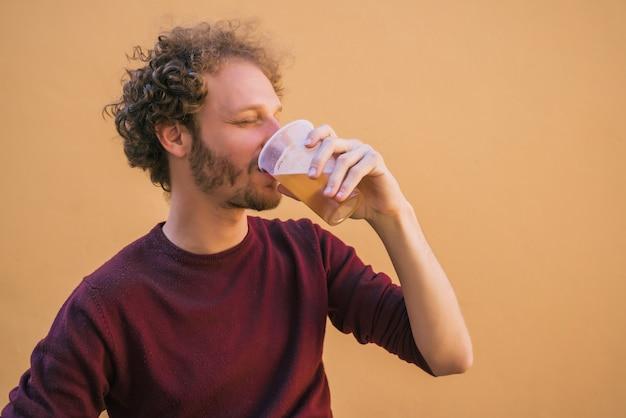 Ritratto di giovane uomo godendo e bevendo birra contro lo spazio giallo. concetto di stile di vita.