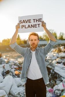 Ritratto di giovane uomo in lotta per la natura tenendo salva la madre terra segno in discarica. protestando contro l'inquinamento della natura agitando le mani chiedendo di salvare il pianeta.