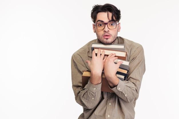 Ritratto di un giovane con gli occhiali che tiene molti libri isolati su un muro bianco