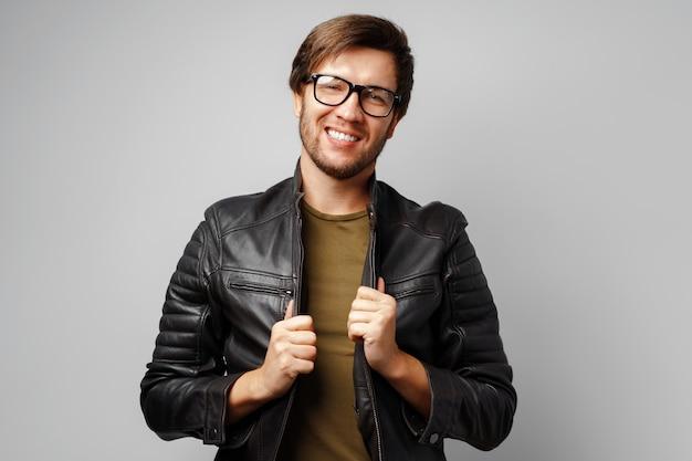 Ritratto di un giovane uomo con gli occhiali che indossa giacca di pelle nera su sfondo grigio si chiuda
