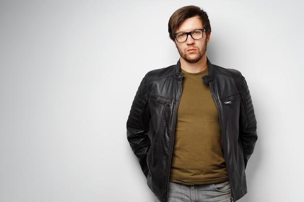 Ritratto di un giovane uomo con gli occhiali che indossa giacca di pelle nera su sfondo grigio
