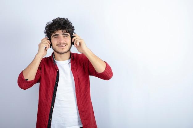 Ritratto di giovane uomo in cuffie ascoltando la canzone sul muro bianco.