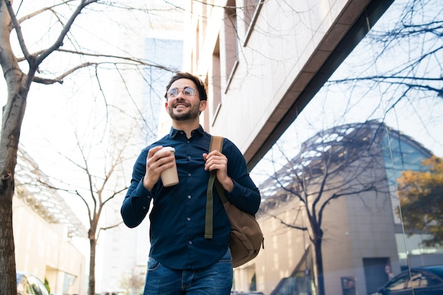 Ritratto di giovane uomo che tiene una tazza di caffè mentre si cammina all'aperto in strada