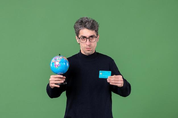 Ritratto di giovane uomo con globo terrestre e carta di credito sfondo verde banca soldi maschio insegnanti natura
