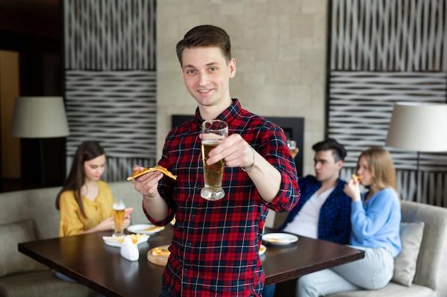 Ritratto di un giovane uomo che tiene pizza e birra in un pub