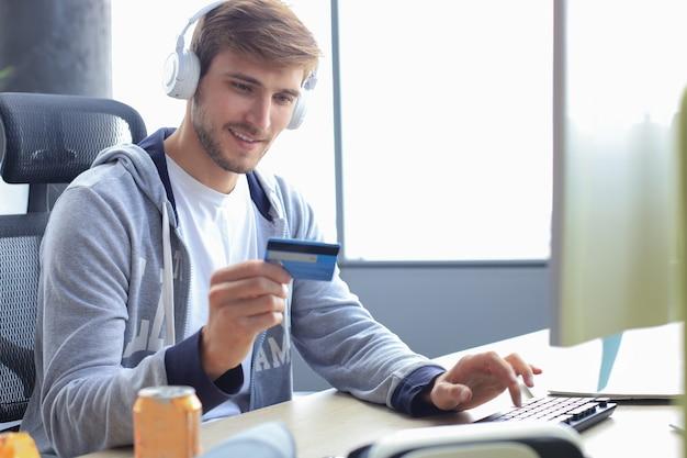 Il ritratto di un giovane tiene e utilizza la carta di credito per ricaricare i soldi del gioco.