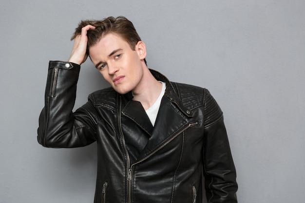 Ritratto di un giovane in giacca di pelle che si tocca i capelli sul muro grigio gray